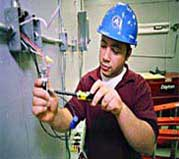 Color image showing an employee performing emergency repairs to electric box in a home